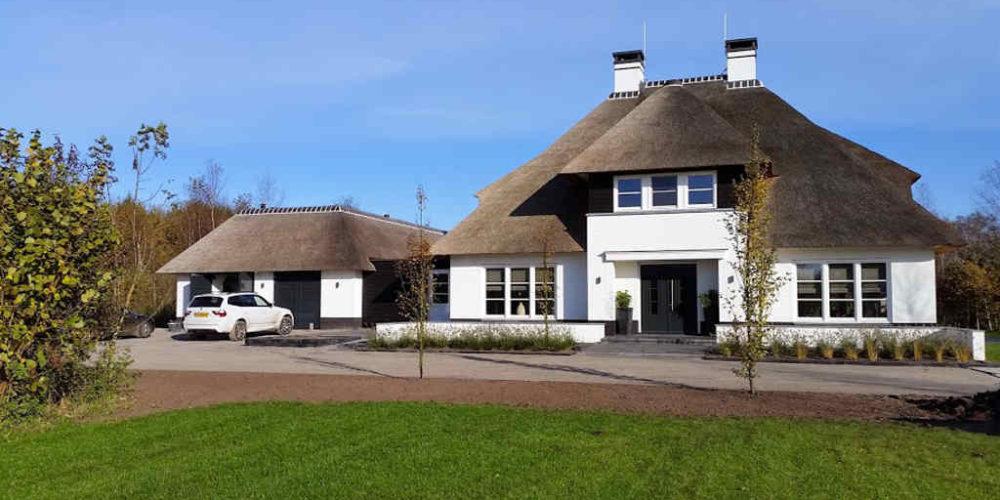 Moderne nieuwbouw villa met rieten kap, een veranda en aangebouwd zwembadgebouw. Ontworpen door Hoogsteder architecten.