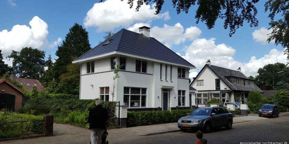 Statige woning in woonwijk met wit gestucte gevels en grijze dakpannen ontworpen door Hoogsteder architecten