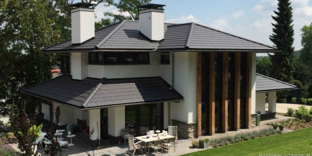 luxe villa met buiten haard, houten details en dakpannen ontworpen door Hoogsteder architecten